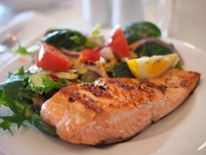 salmon-with-vegetables-and-lemon-on-white-table